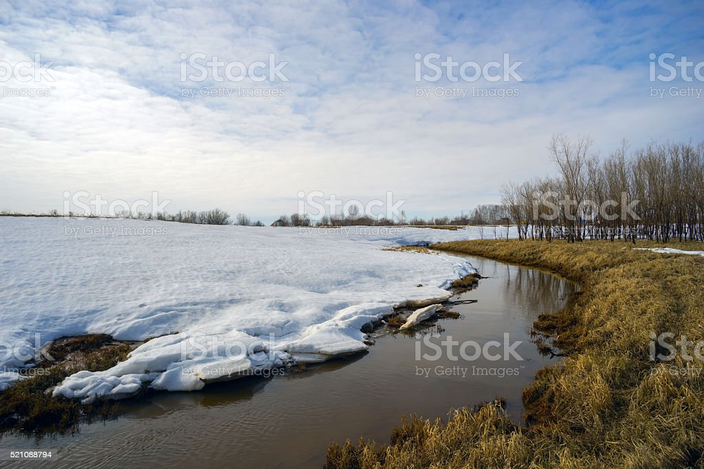 Spring landscape with a brook behind snow mound stock photo