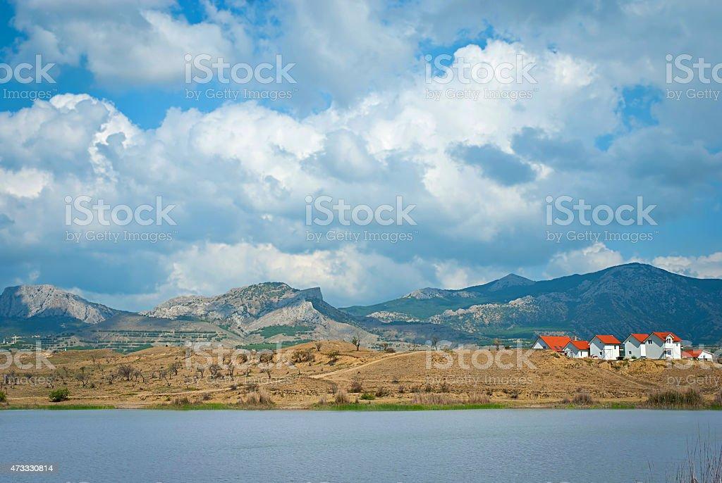 Paysage de printemps avec des maisons, les montagnes et les nuages dans le ciel photo libre de droits