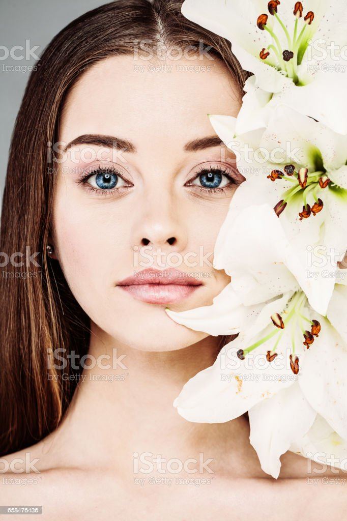 Spring or Summer Portrait of Beautiful Woman with Natural Makeup and White Lily Flowers stock photo