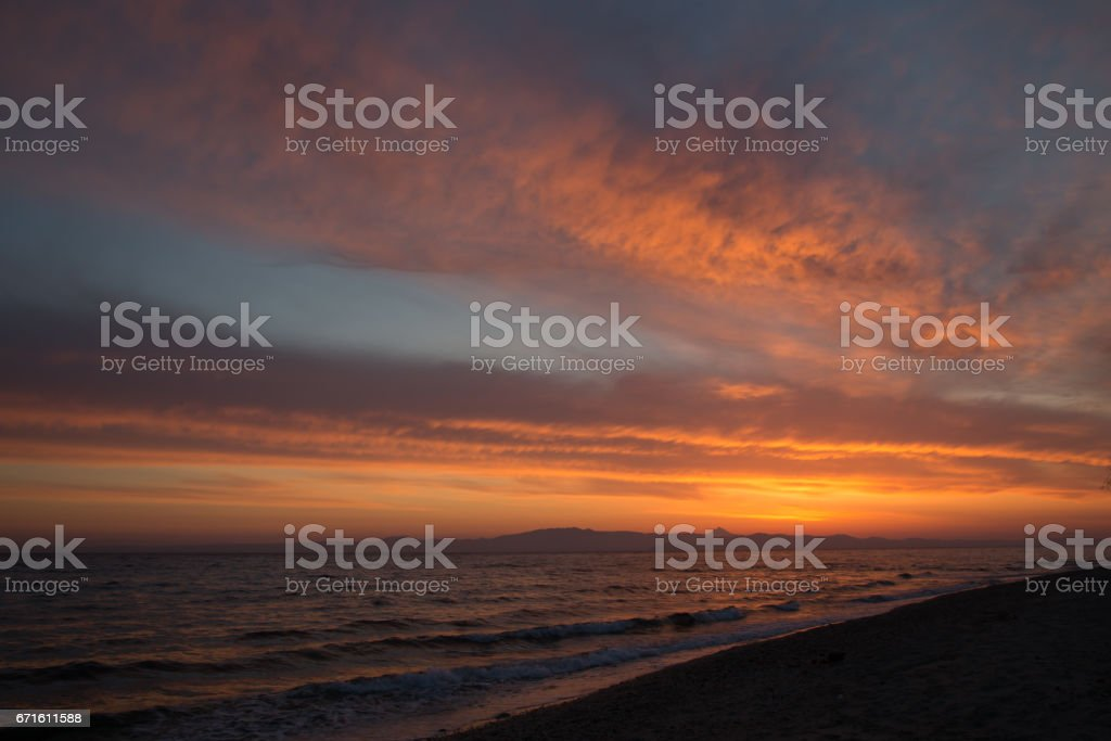 Spring orange dawn on the shore of the calm sea during the tide. stock photo