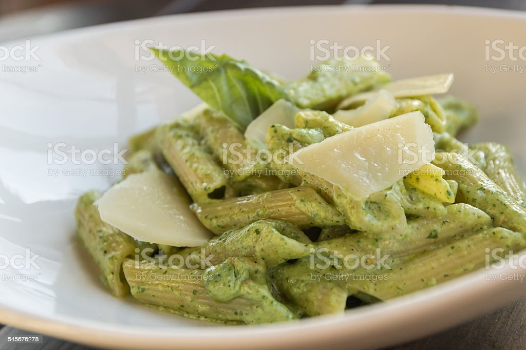 Spring penne with spinach pesto and green pea stock photo