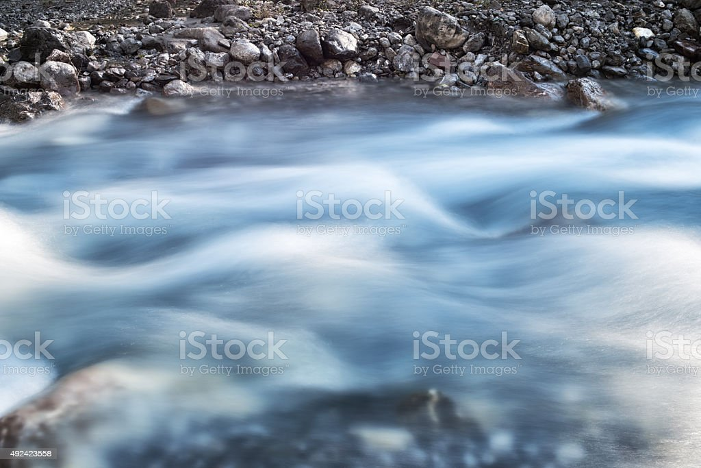 spring riverbed with stones and pebbles in the alps stock photo