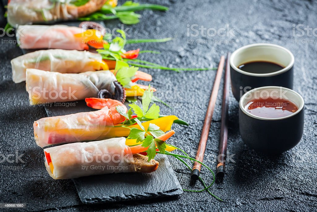 Spring rolls served with soy sauce on a stone plate stock photo