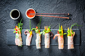 Spring rolls served with soy sauce on a stone plate
