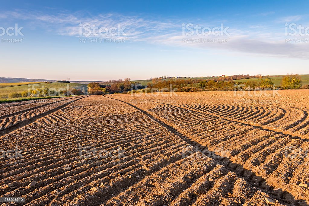 Spring rural countryside with ruts in plowed field stock photo