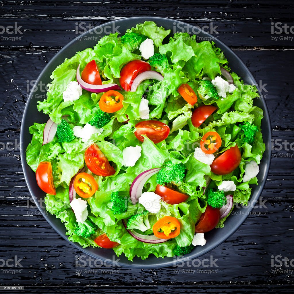 Spring salad shot from above on black wood table stock photo