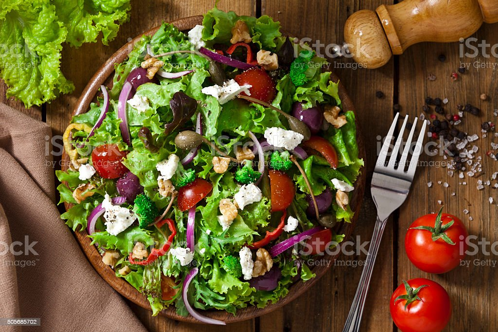 Spring salad shot from above on rustic wood table stock photo