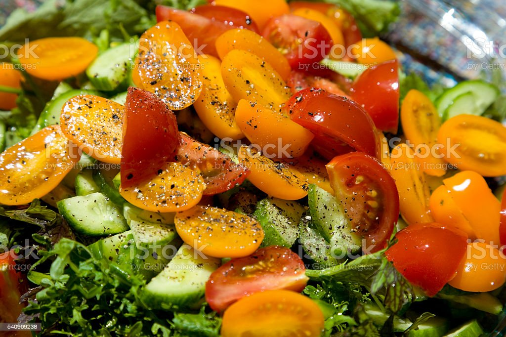 Spring salad with tomatoes, cucumbers and spring greens stock photo