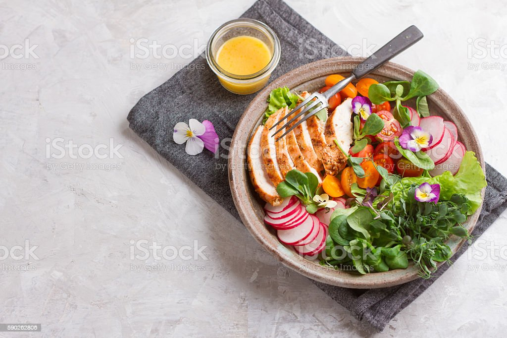 Spring salad with vegetables, chicken breast and edible flowe stock photo