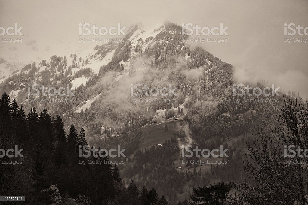 Spring Snowfall in Swiss Alps, farms on hillside royalty-free stock photo