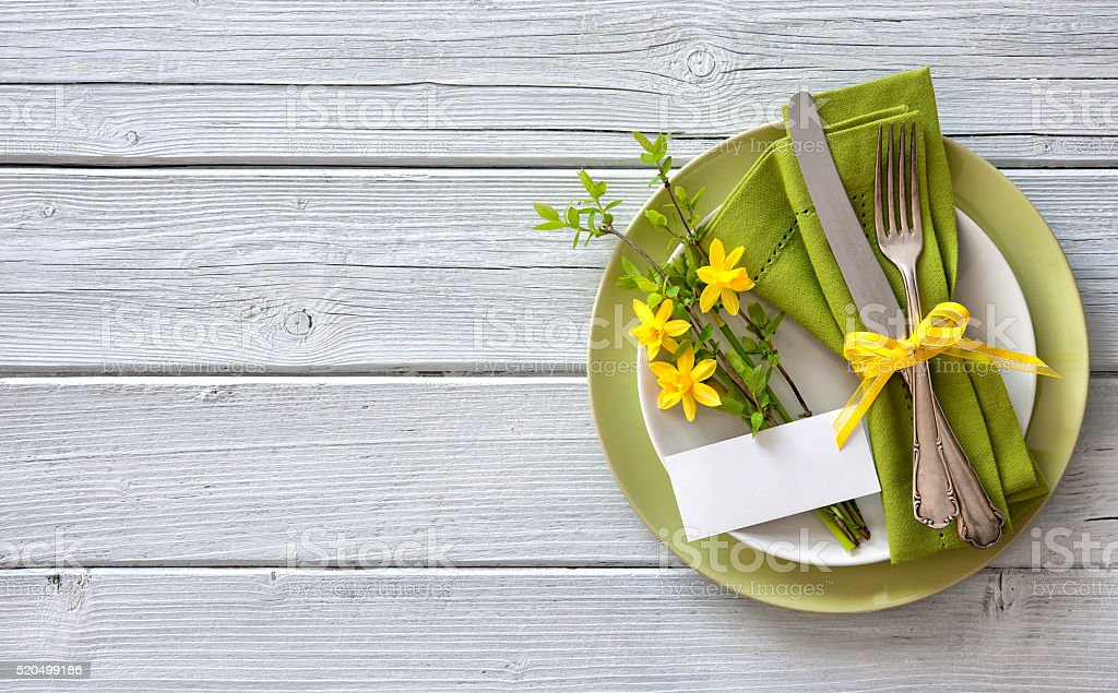 Spring table place setting with daffodils stock photo