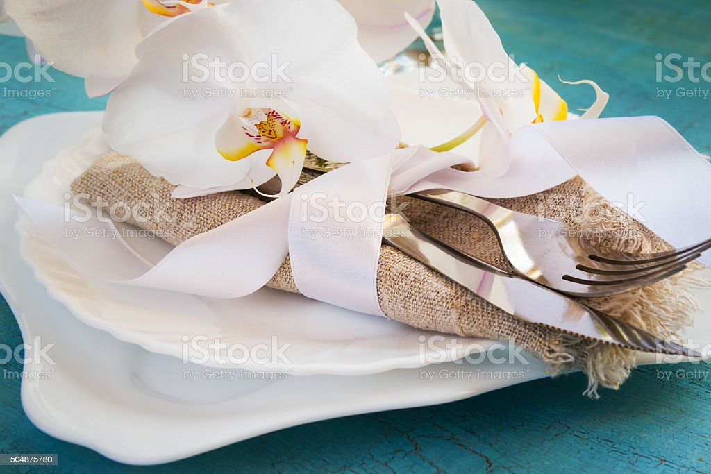 Spring table setting with White orchid decorations and napkins o stock photo