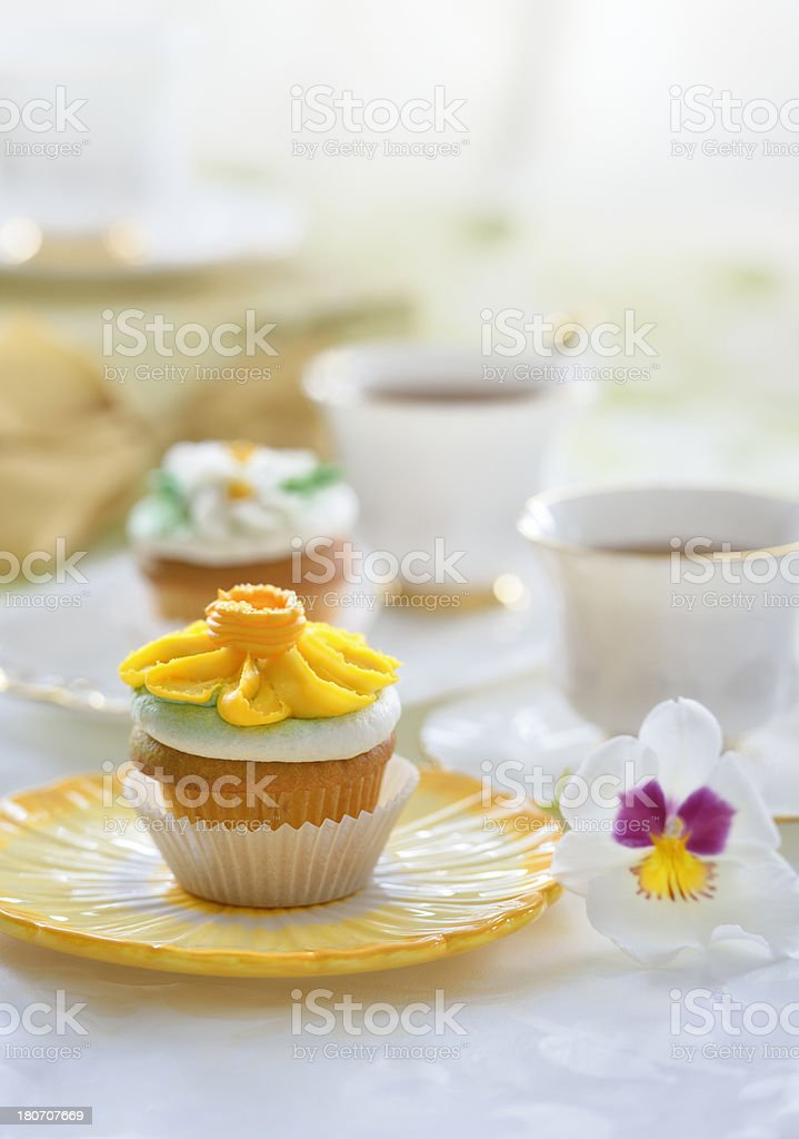 Spring tea party - yellow daisy cupcake and teacups royalty-free stock photo