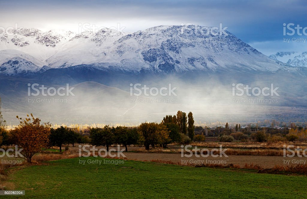 Spring Time Rural land and Snowy Mountains stock photo