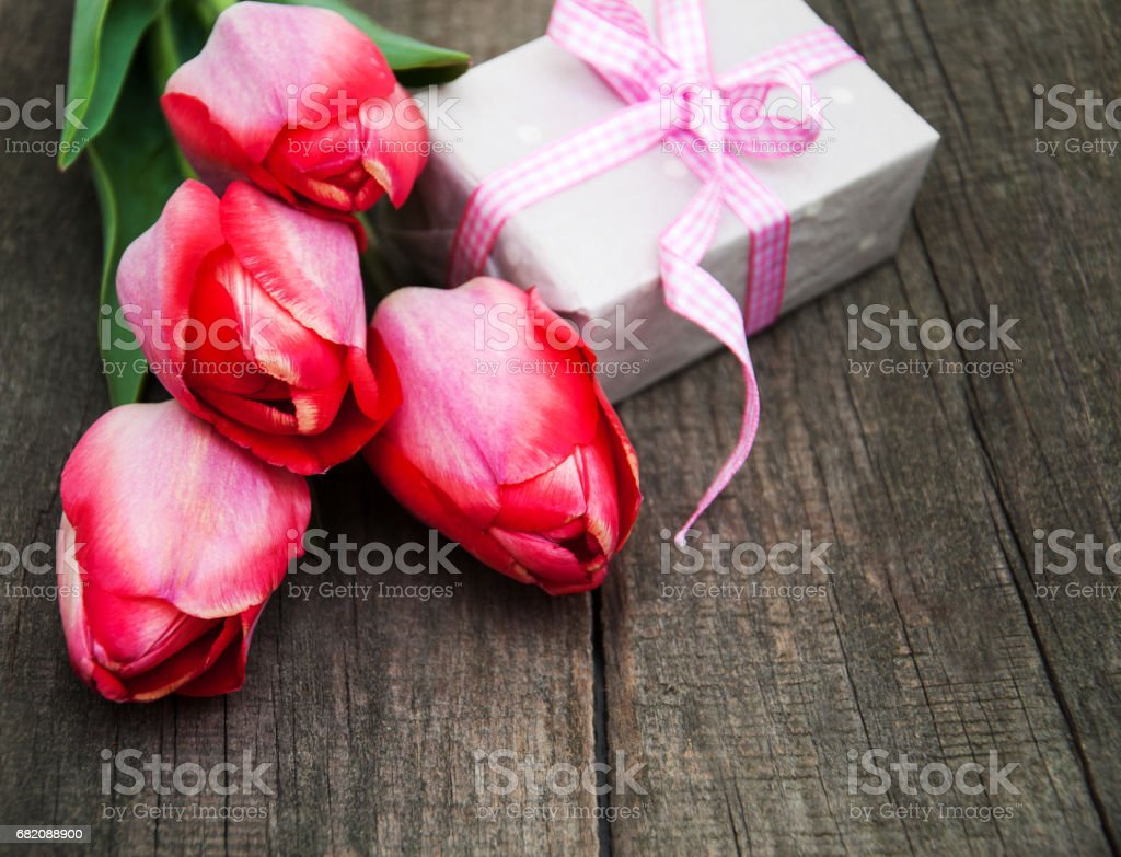 Spring tulips flowers and gift box on a old wooden background