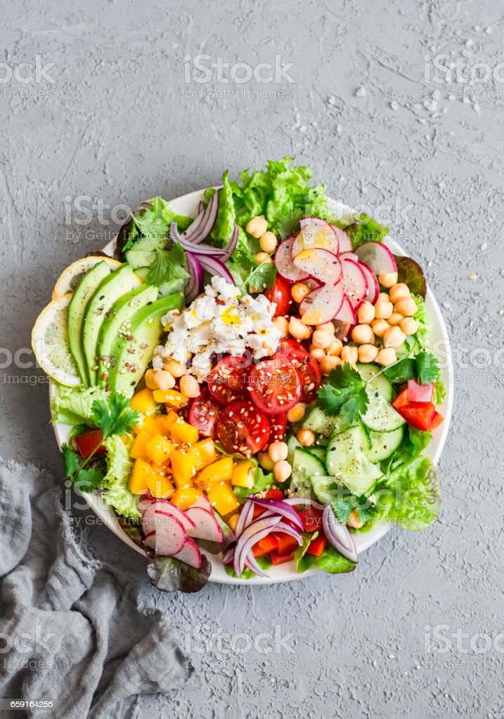 Spring vegetable buddha bowl. Salad with veggies, chickpeas, avocado and feta. Delicious healthy food.  On a gray background, top view stock photo
