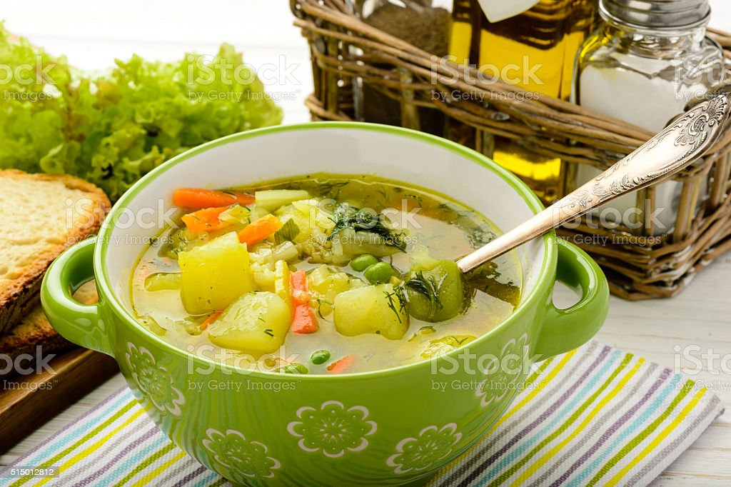 Spring vegetable soup in green bowl. stock photo