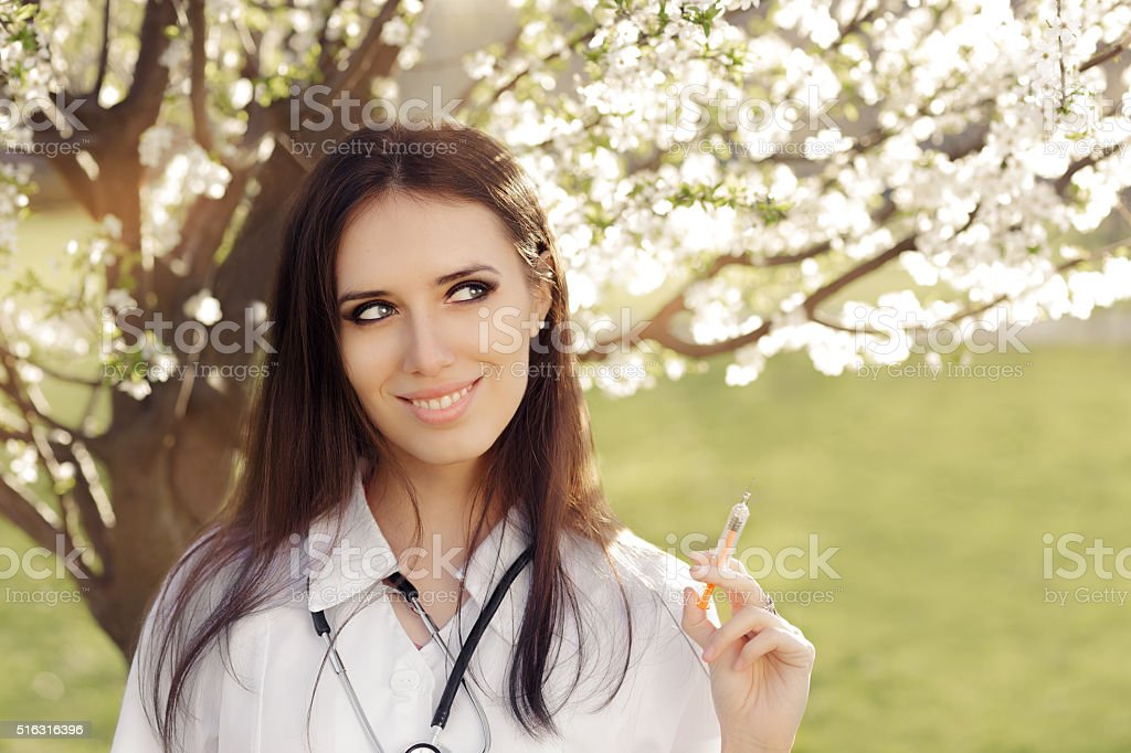 Spring Woman Doctor Smiling and Holding Vaccine Syringe stock photo