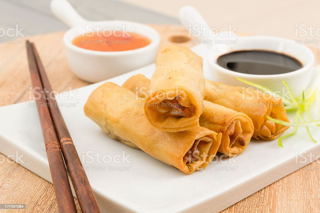 Springs rolls on white tray with chopsticks and sauces stock photo