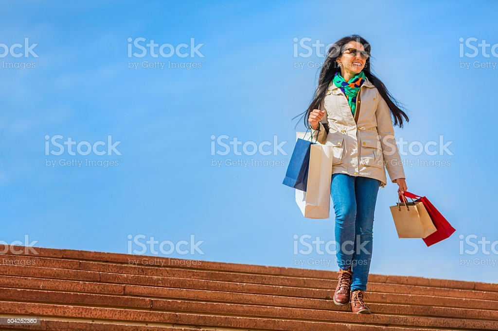Springtime shopping. Hispanic young woman walking with bags on stairway stock photo