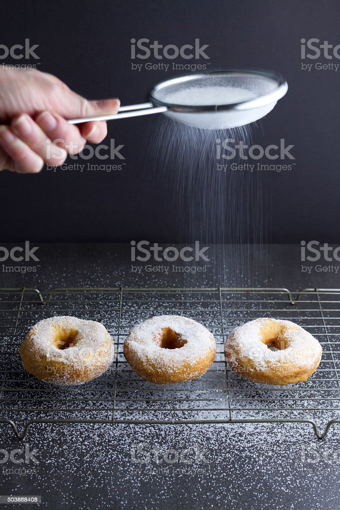 Sprinking sugar on 3 ring doughnuts stock photo
