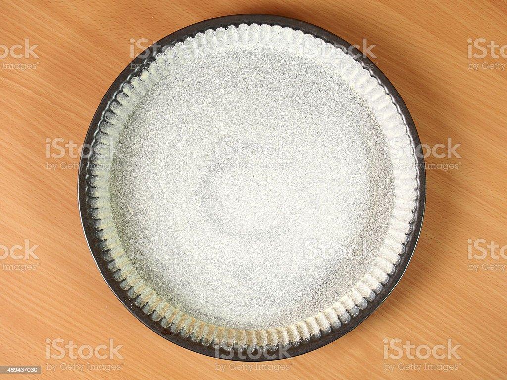Sprinkle tart pan with semolina flour stock photo