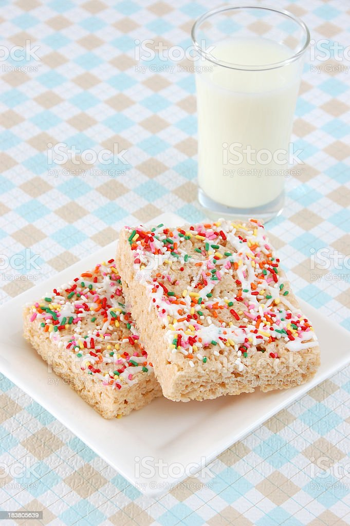 Sprinkled rice crispy treats on plate with glass of milk stock photo