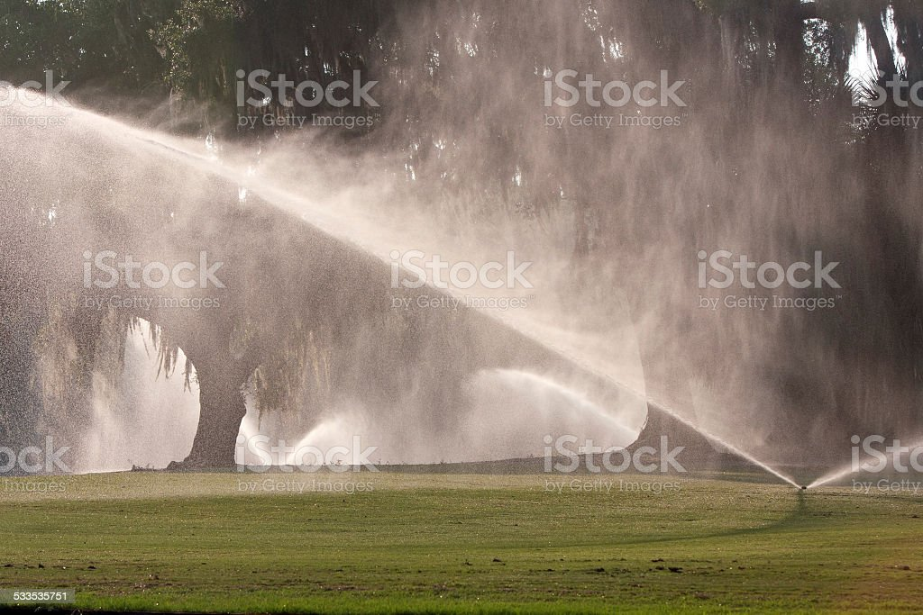 Sprinklers Pour Water Onto Golf Course Fairway stock photo