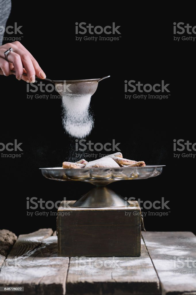 Sprinkling cookies with powdered sugar stock photo