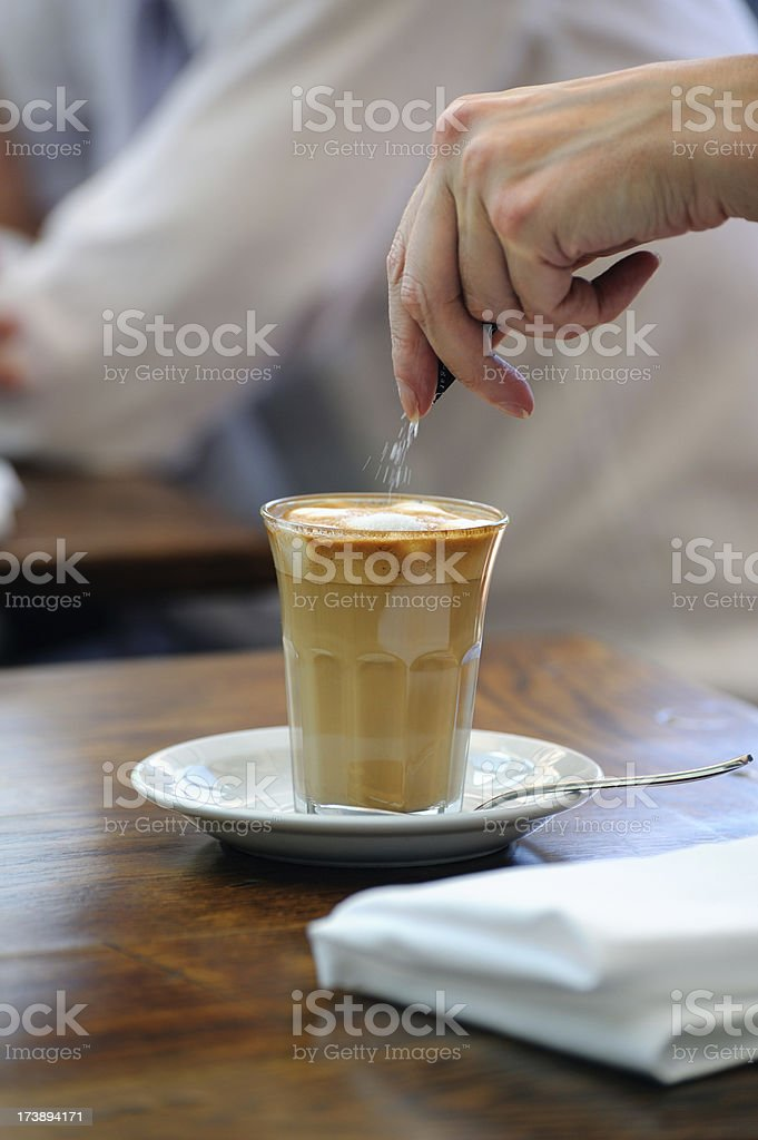 Sprinkling Sugar into Latte stock photo
