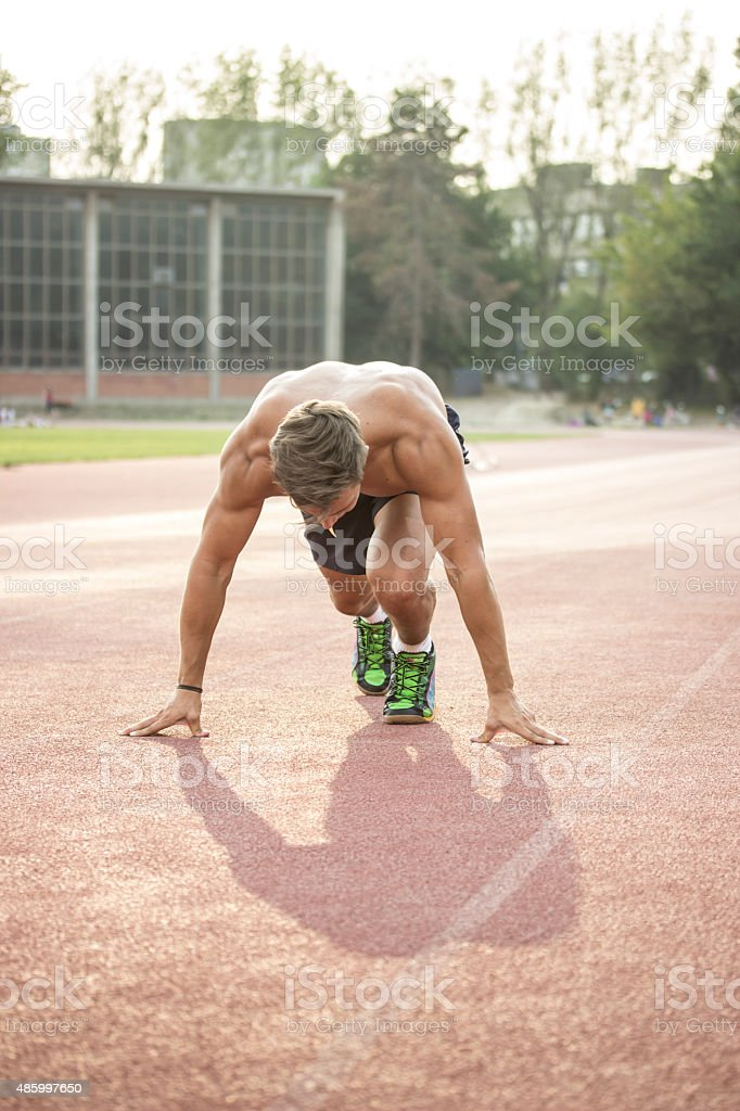 Sprinter at start position, kneeling, muscular body. stock photo