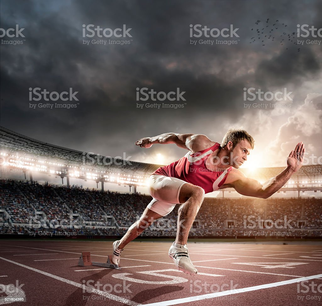 Sprinter Bursting from Starting Blocks on Track stock photo