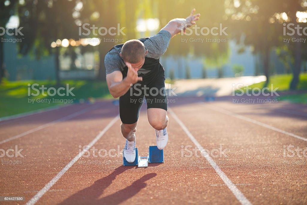 Sprinter leaving starting blocks on the running track. Explosive start. stock photo