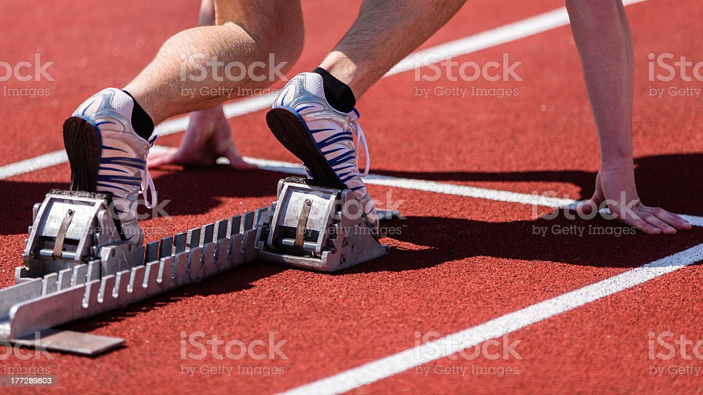 A sprinter waiting to begin the race in track and field royalty-free stock photo