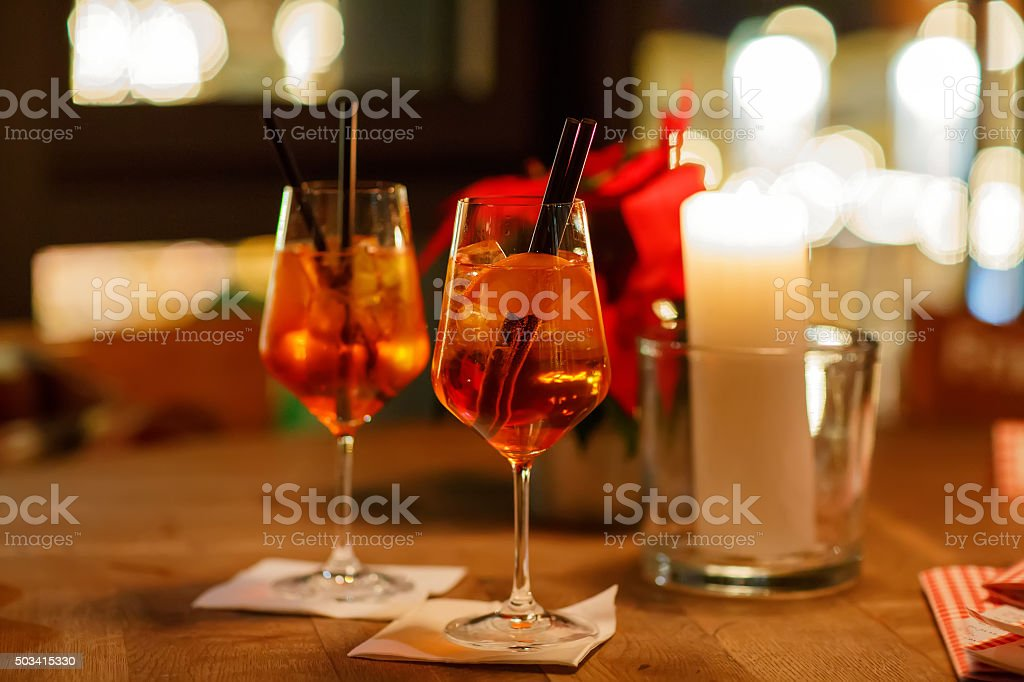 Aperol Spritz Cocktai on table with ice cubes and oranges stock photo