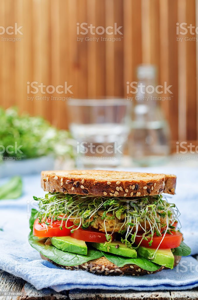 sprouts avocado tomato spinach chickpeas burger rye sandwich stock photo
