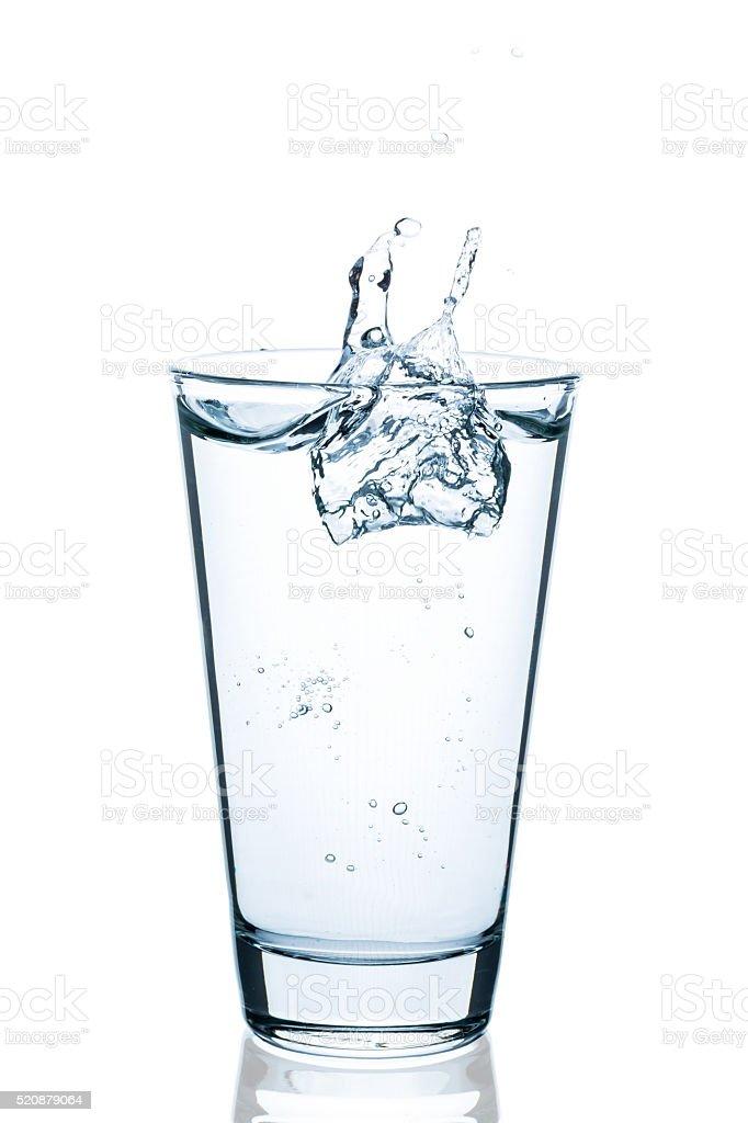 Sprudelndes Glas Wasser mit Spritzer und Tropfen stock photo