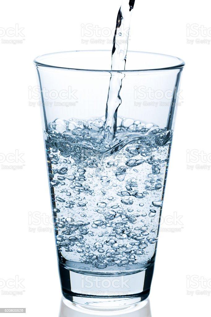 sprudelndes Wasser in halbvolles Glas eingießen stock photo