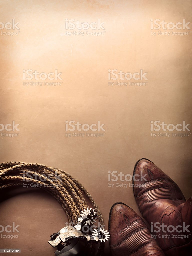 Spurs next to cowboy boots and lasso on leather surface stock photo
