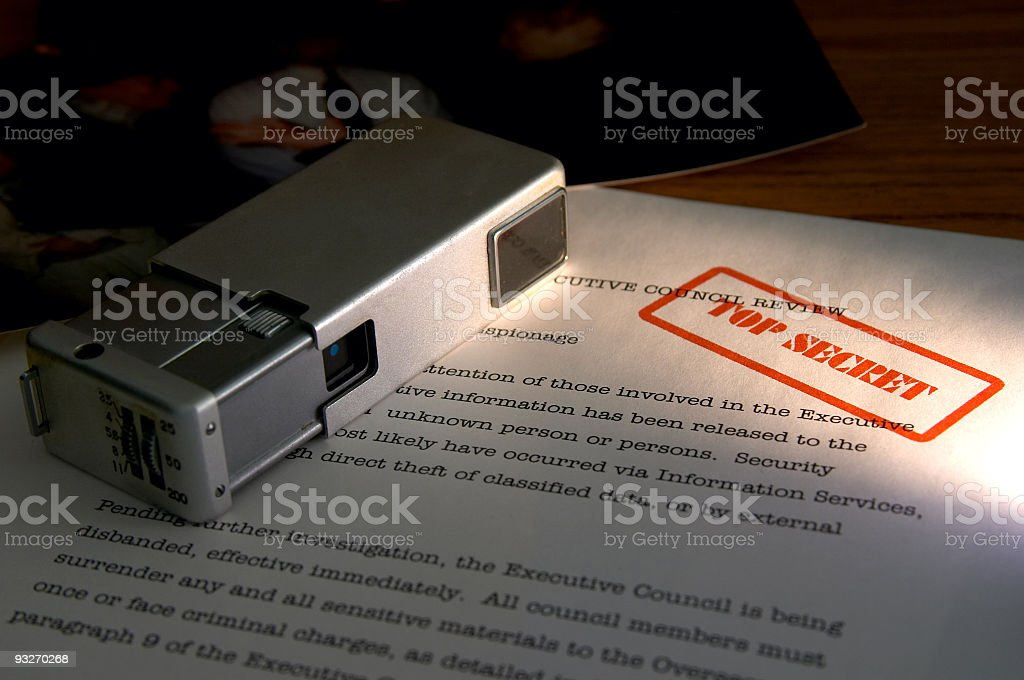 A spy camera sitting on top of top secret documents royalty-free stock photo