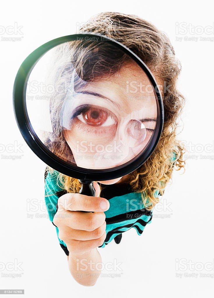 I spy! Pretty girl with magnifying glass hugely enlarging eye stock photo