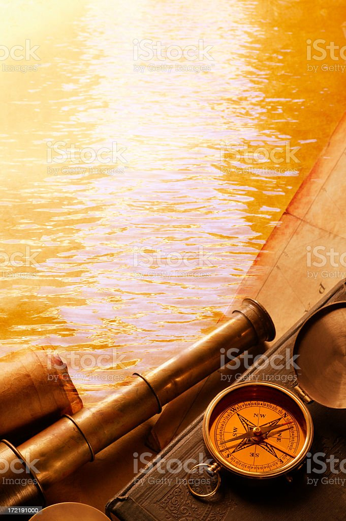 Spyglass and compass with water in background stock photo