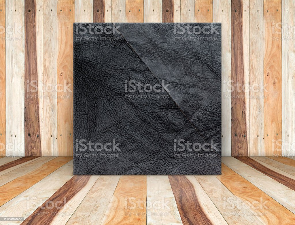 Square black leather canvas leaning at wood plank floor stock photo