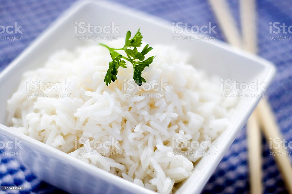 A square bowl of rice beside chopsticks royalty-free stock photo