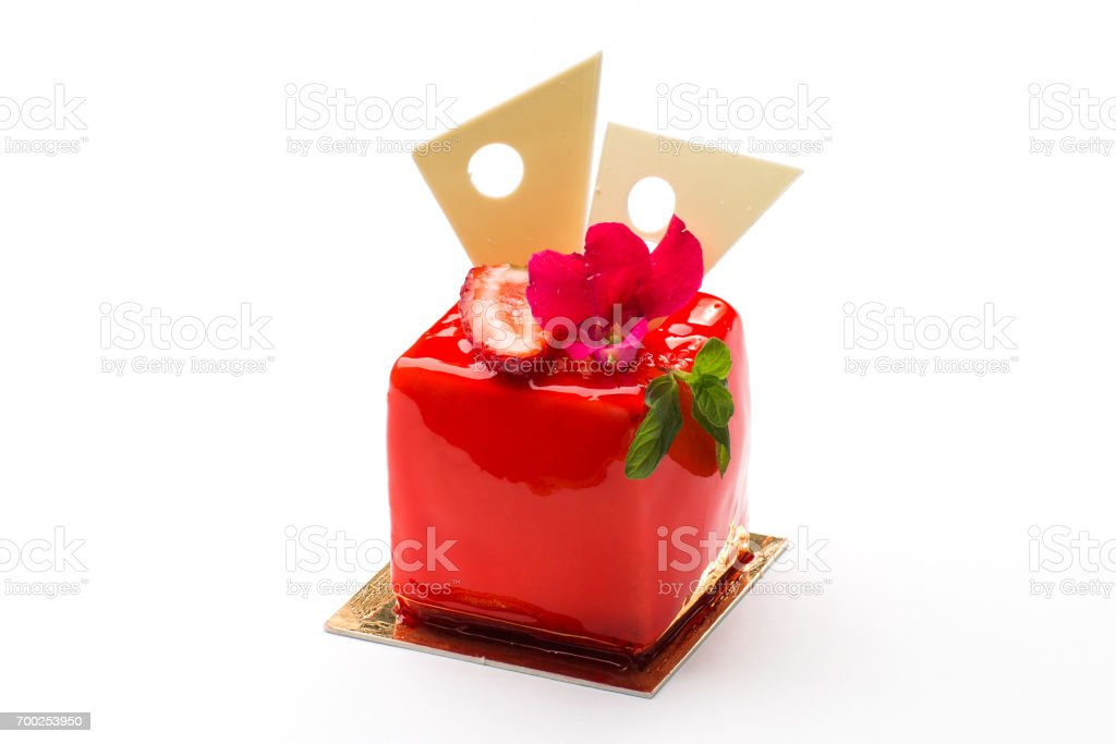 Square cake in red glaze with strawberries and mint leaves stock photo