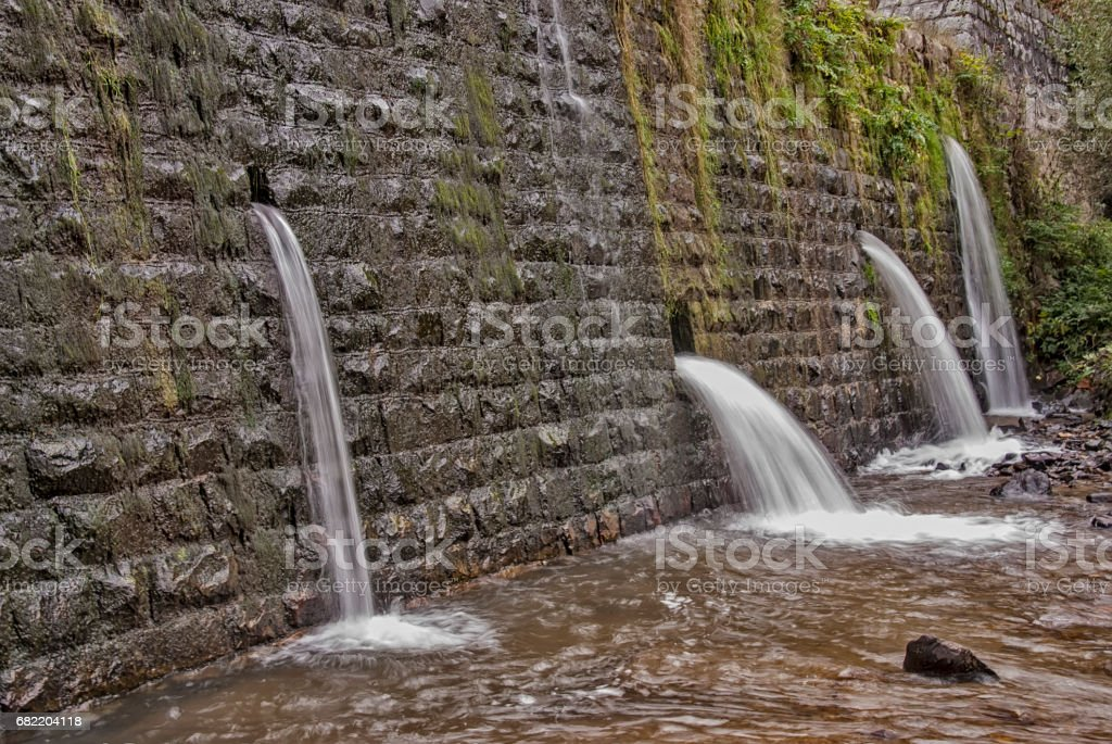 Square concrete blocks dam on the river with holes for drain water stock photo