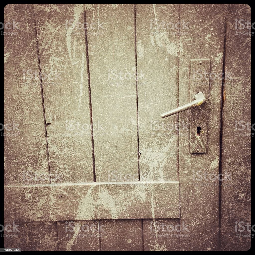 Square detail of locked  wooden door with handle and keyholee stock photo