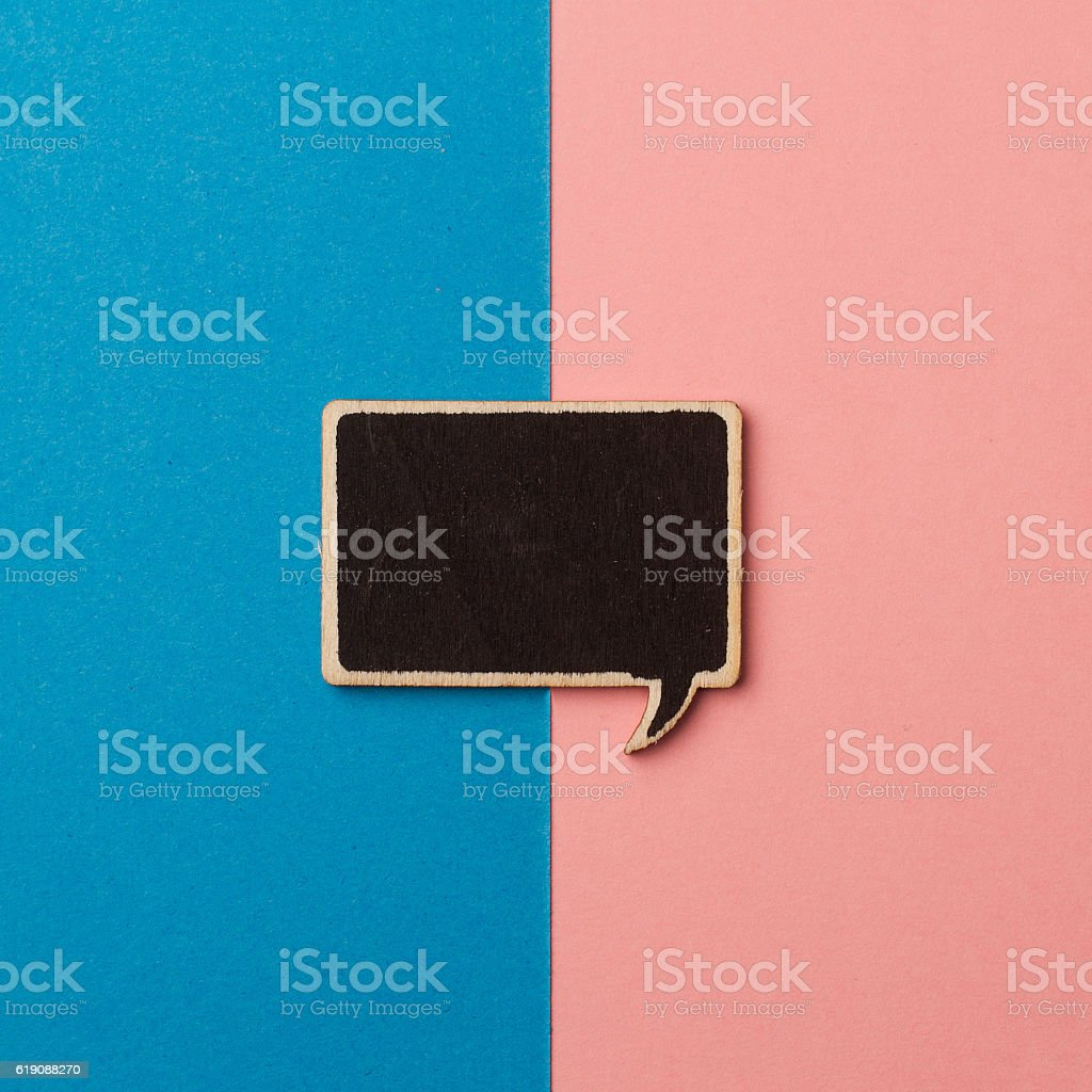 square empty chalkboard wooden speech bubble on pink and blue stock photo