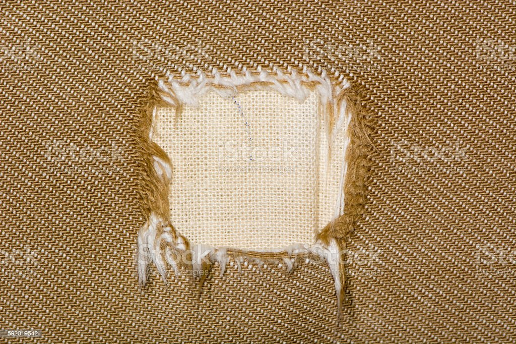 Square hole in fabric of sofa stock photo