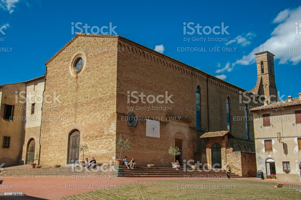 Square view of the church of Sant'Agostino with people in San Gimignano stock photo